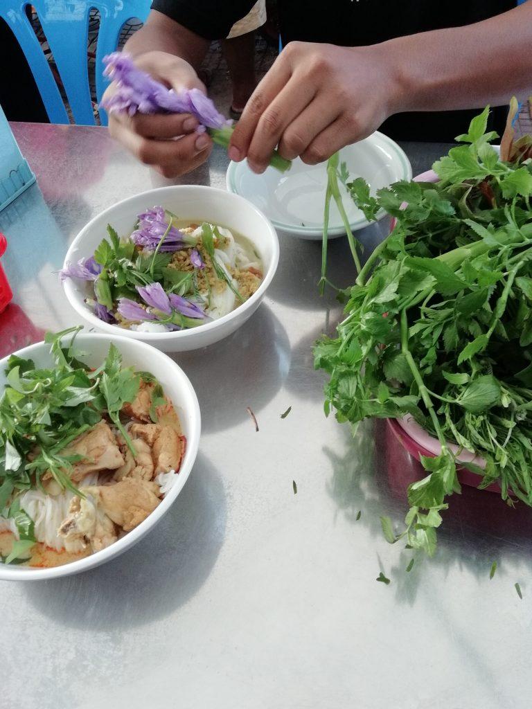 garnishing a bowl of num banh chok