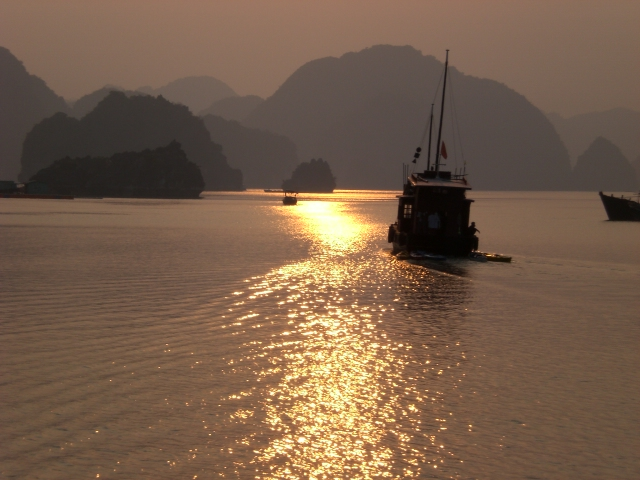 Junk boat sailing into the sunset at Ha Long in Vietnam