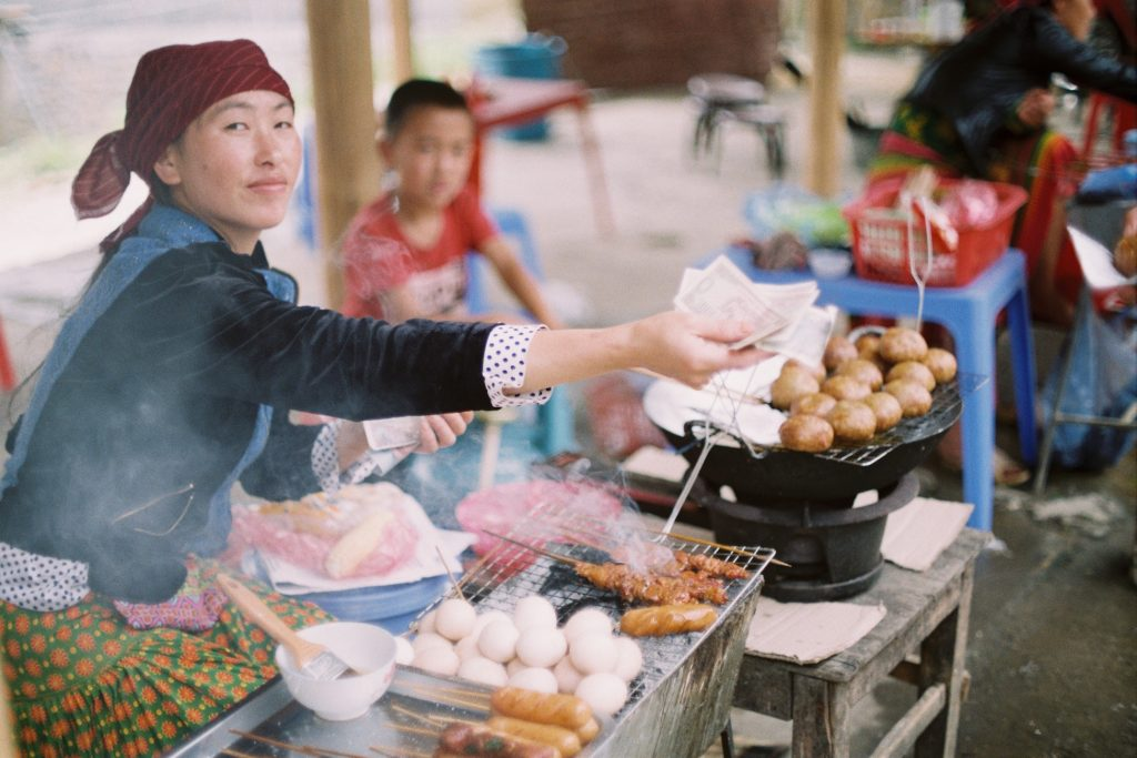 Woman selling food at the Ha Giang market in Vietnam